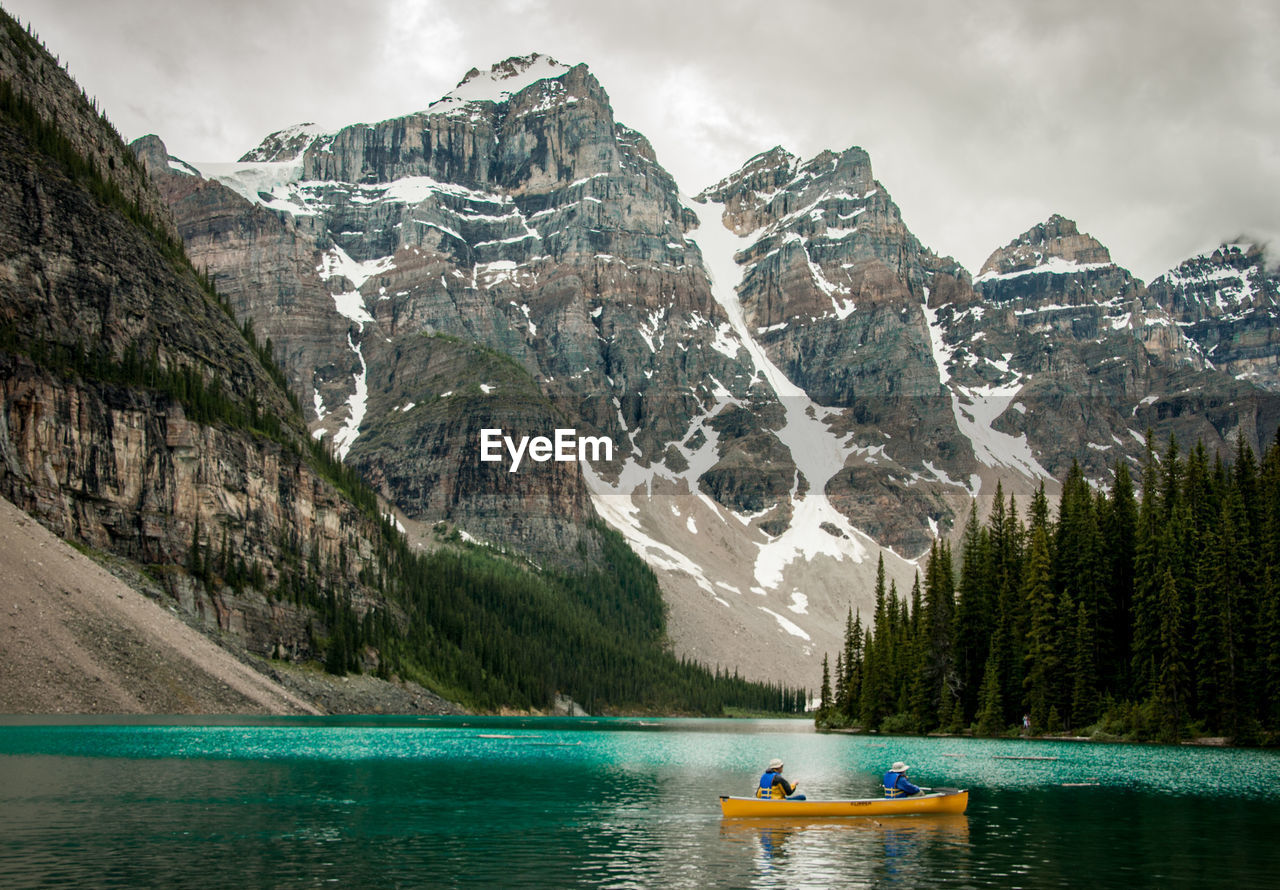 People sailing boat in lake against mountains