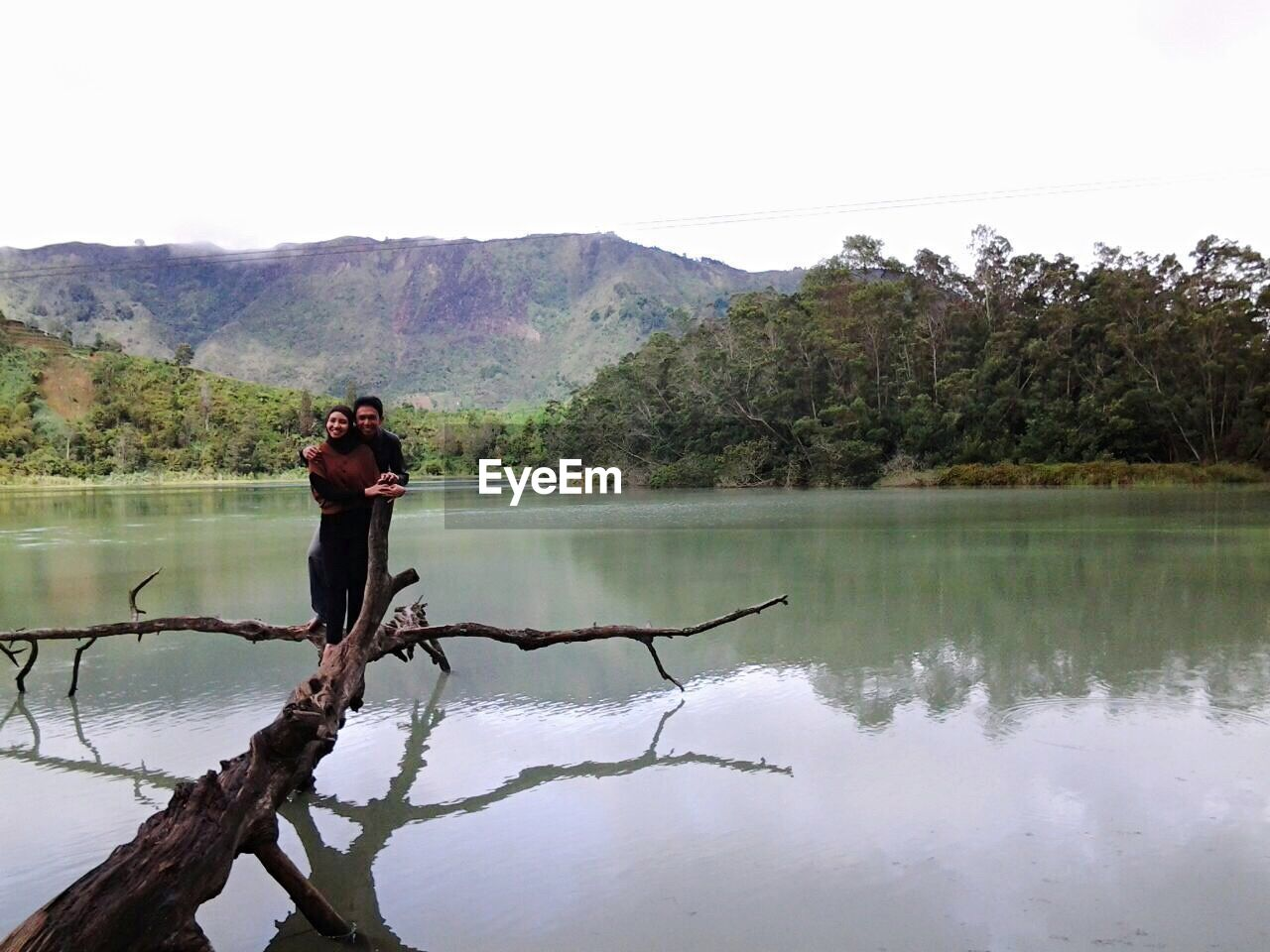 Happy Man And Woman Standing On Fallen Tree Over Calm Lake