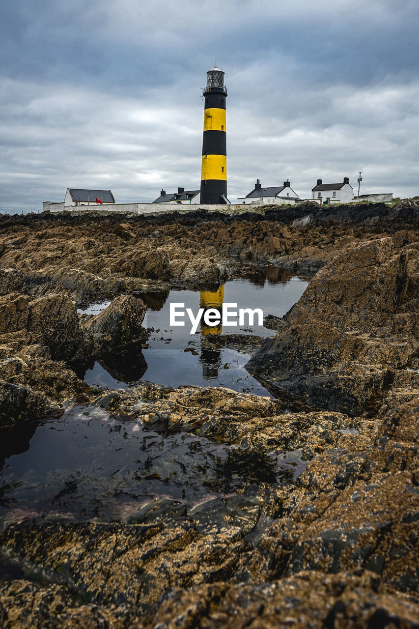 water, sky, cloud - sky, no people, guidance, safety, nature, solid, rock, security, protection, rock - object, land, direction, built structure, day, beach, puddle, outdoors, mud, surface level