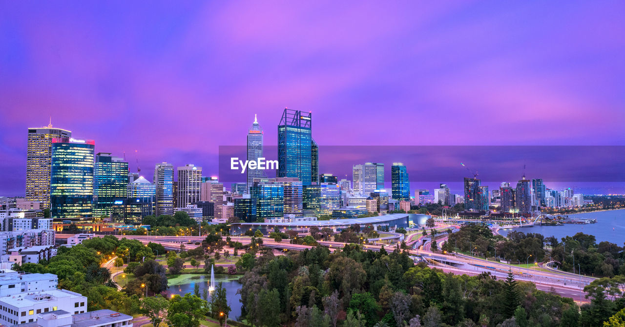 building exterior, city, built structure, architecture, sky, building, office building exterior, cityscape, modern, skyscraper, nature, no people, tower, tall - high, office, tree, cloud - sky, landscape, urban skyline, illuminated, outdoors, financial district, purple
