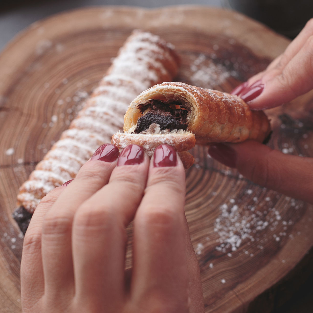 Cropped Image Of Woman Breaking Pastry Over Serving Board