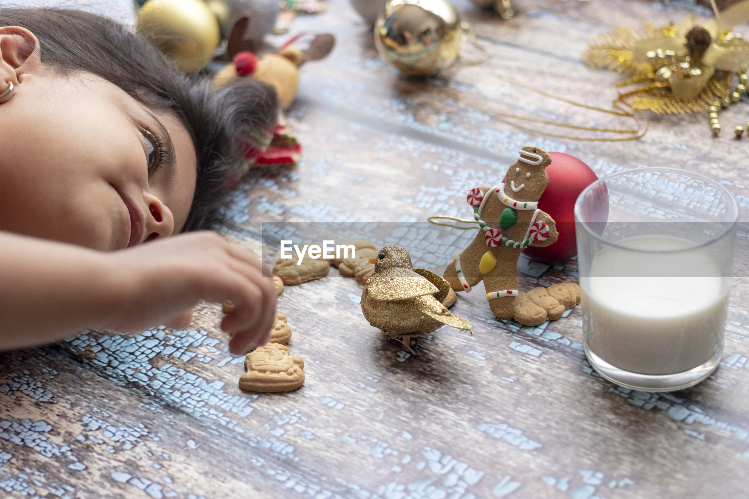 Close-up of girl lying down by baked cookies on wooden flooring