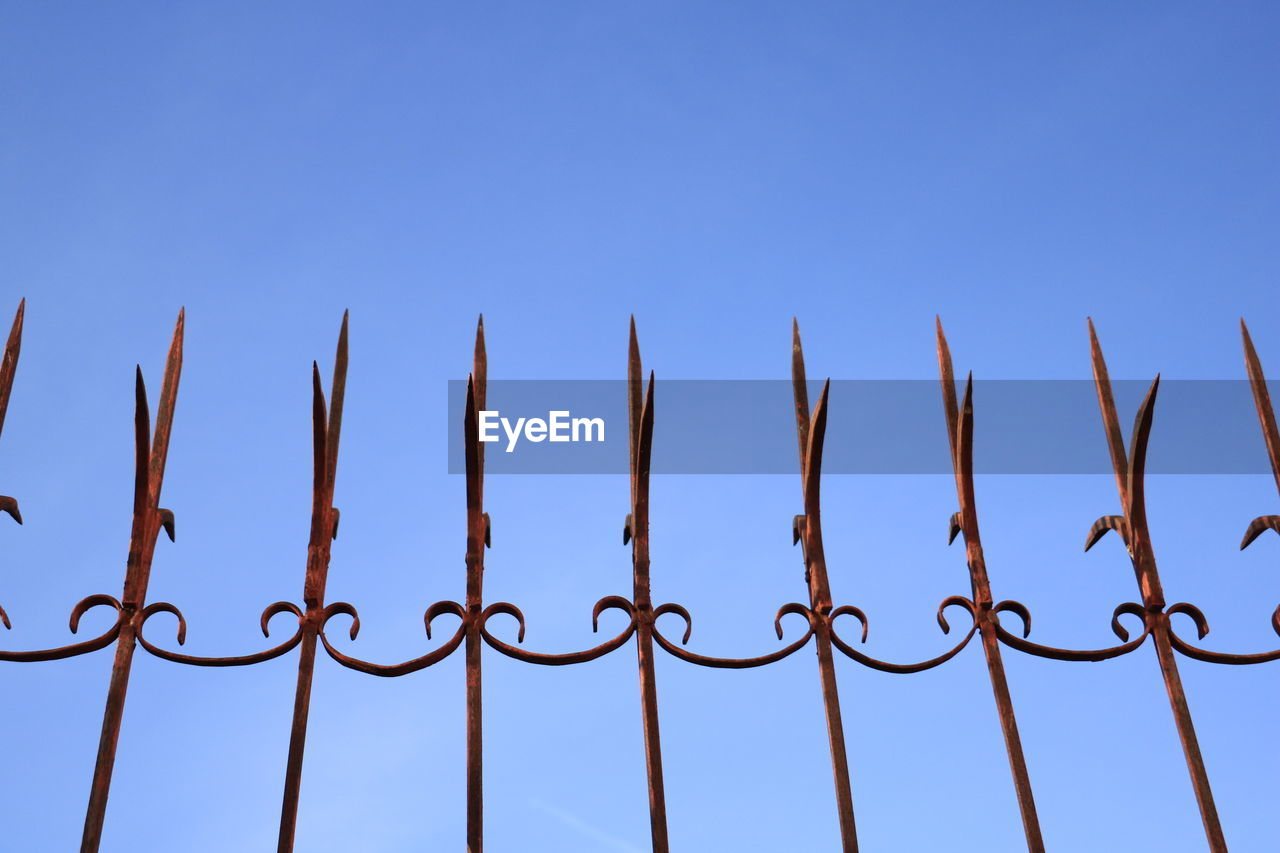 sky, metal, protection, clear sky, security, blue, safety, low angle view, copy space, fence, barrier, no people, boundary, nature, day, pattern, close-up, sharp, communication, outdoors, steel, alloy