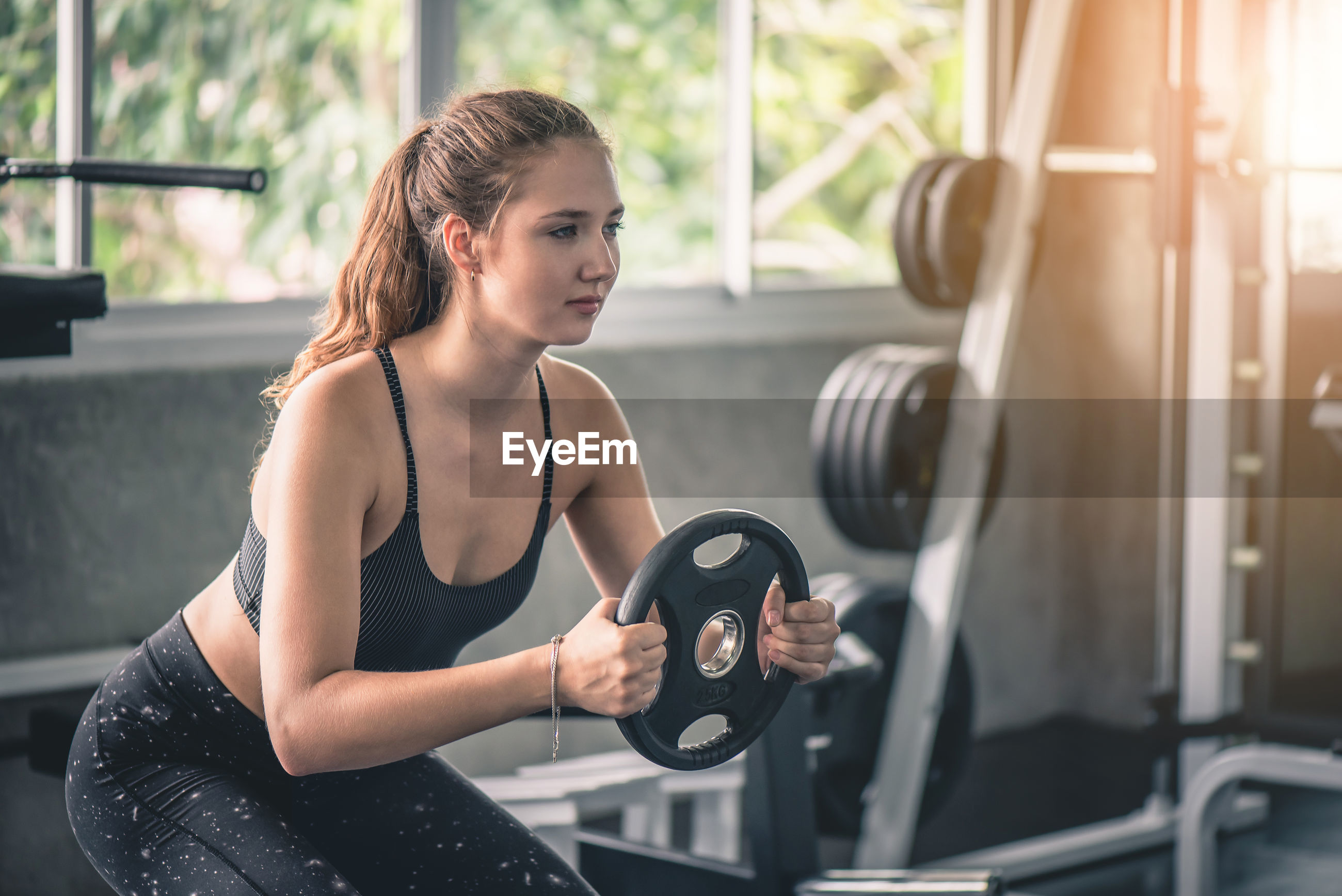 Young woman exercising with weight in gym