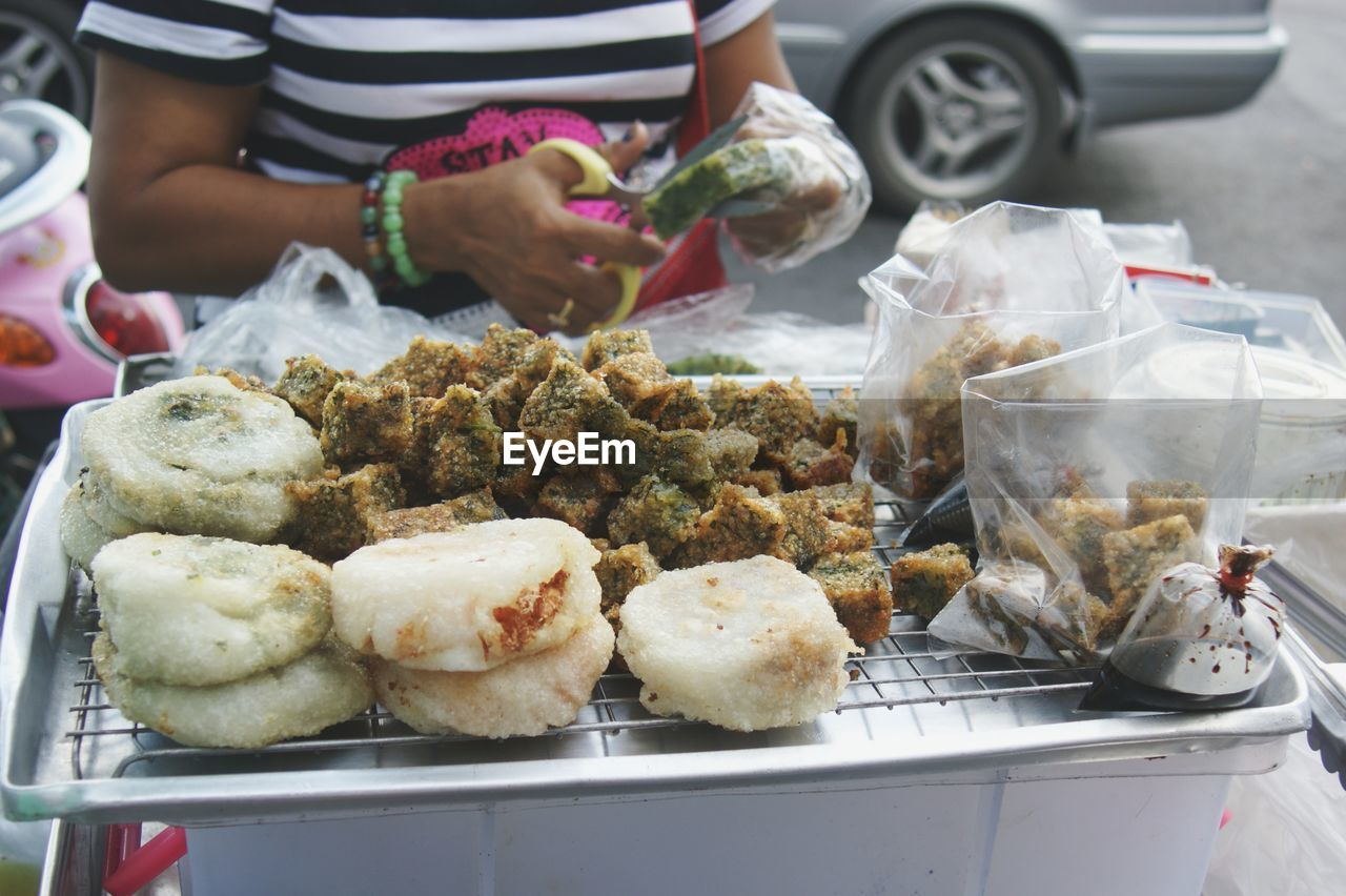 Midsection of woman selling food at market