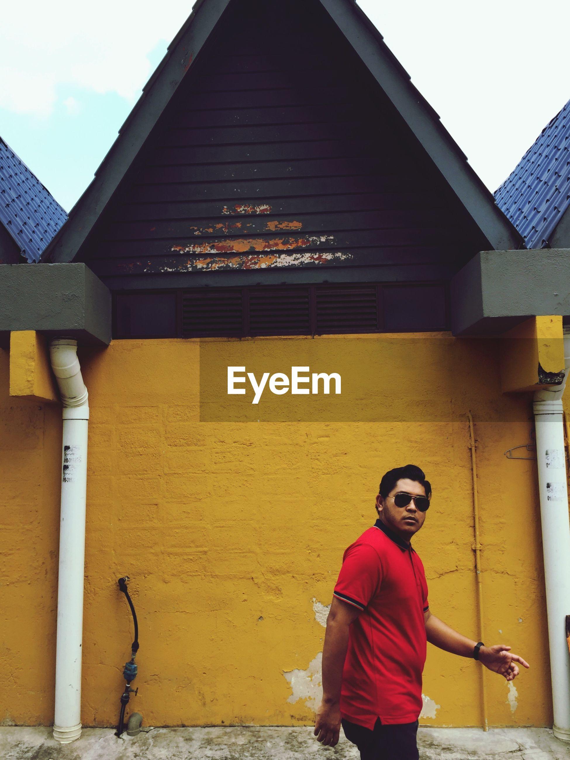 Portrait of man walking by house
