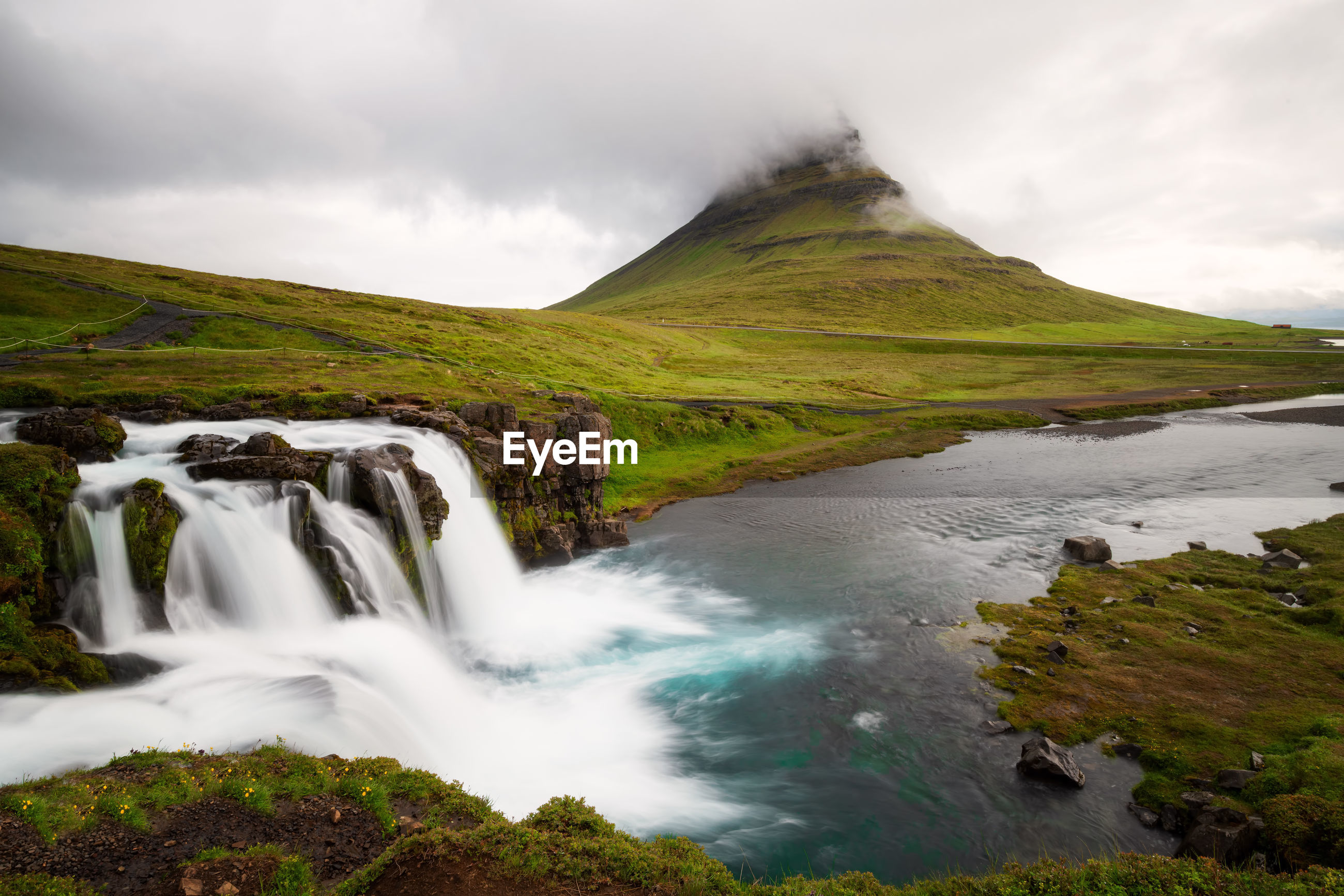 Scenic view of waterfall and mountain against sky