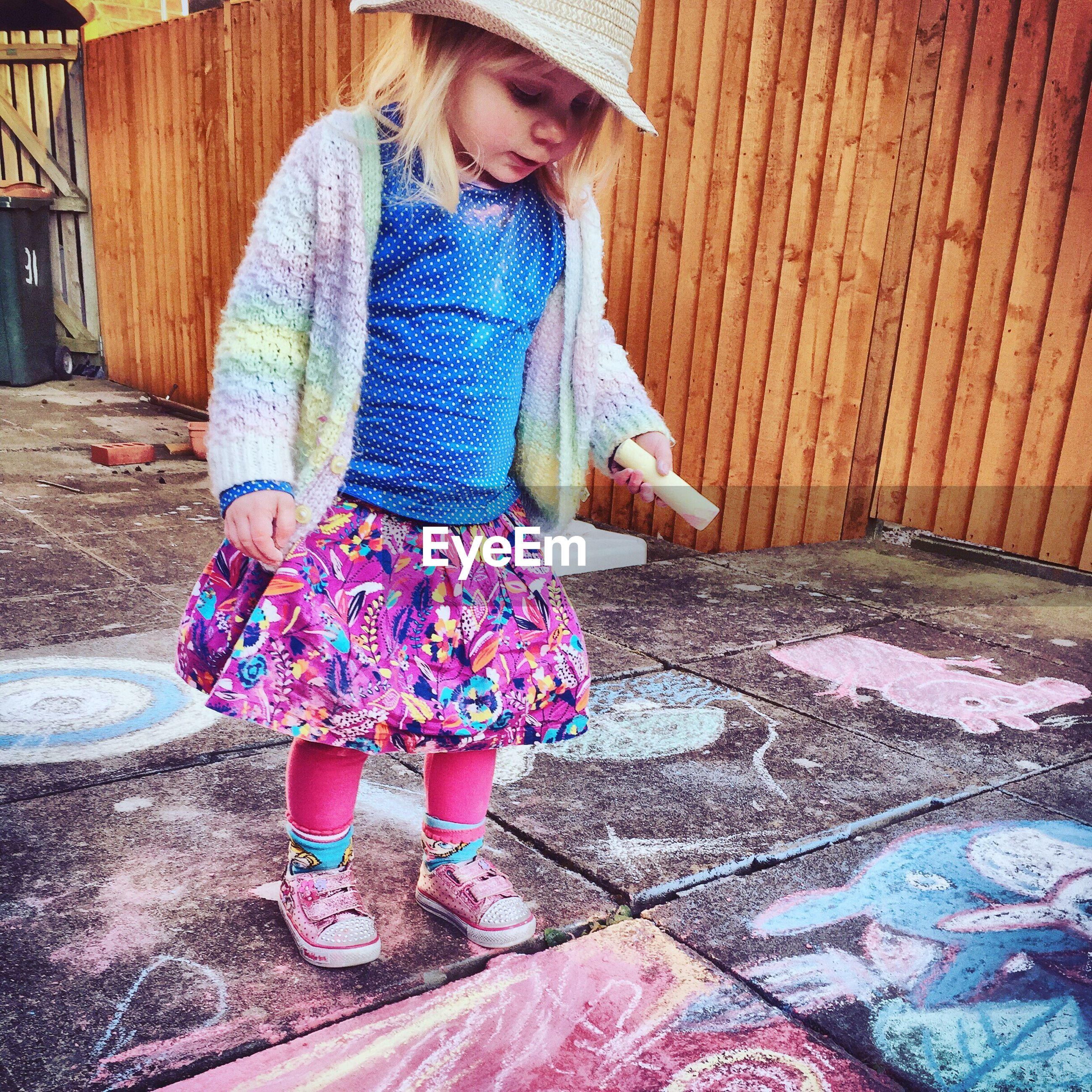 Cute girl doing chalk drawing on sidewalk