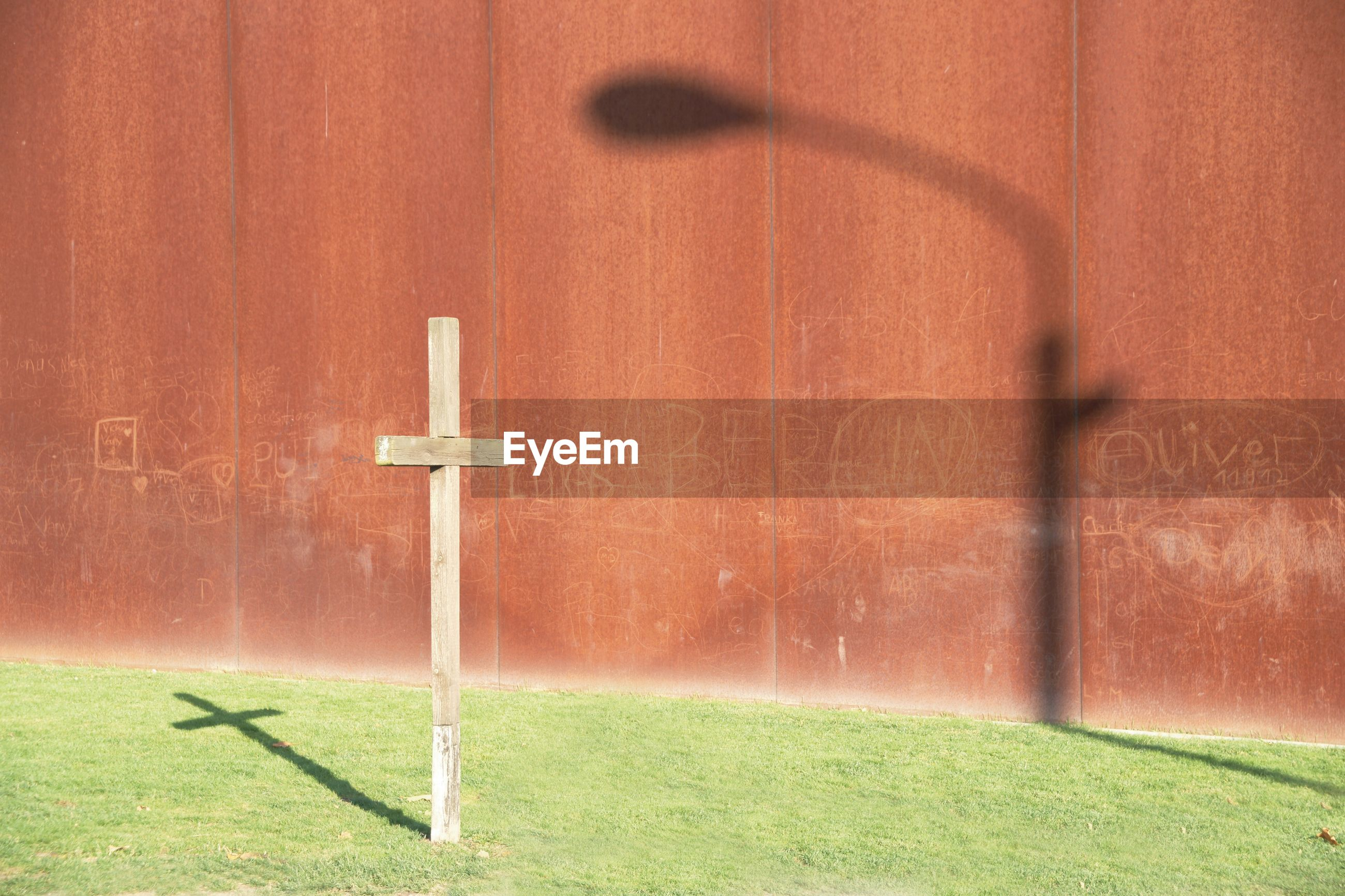 Cross with shadow of street light on brown wall