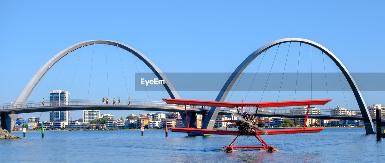Airplane on river against clear blue sky
