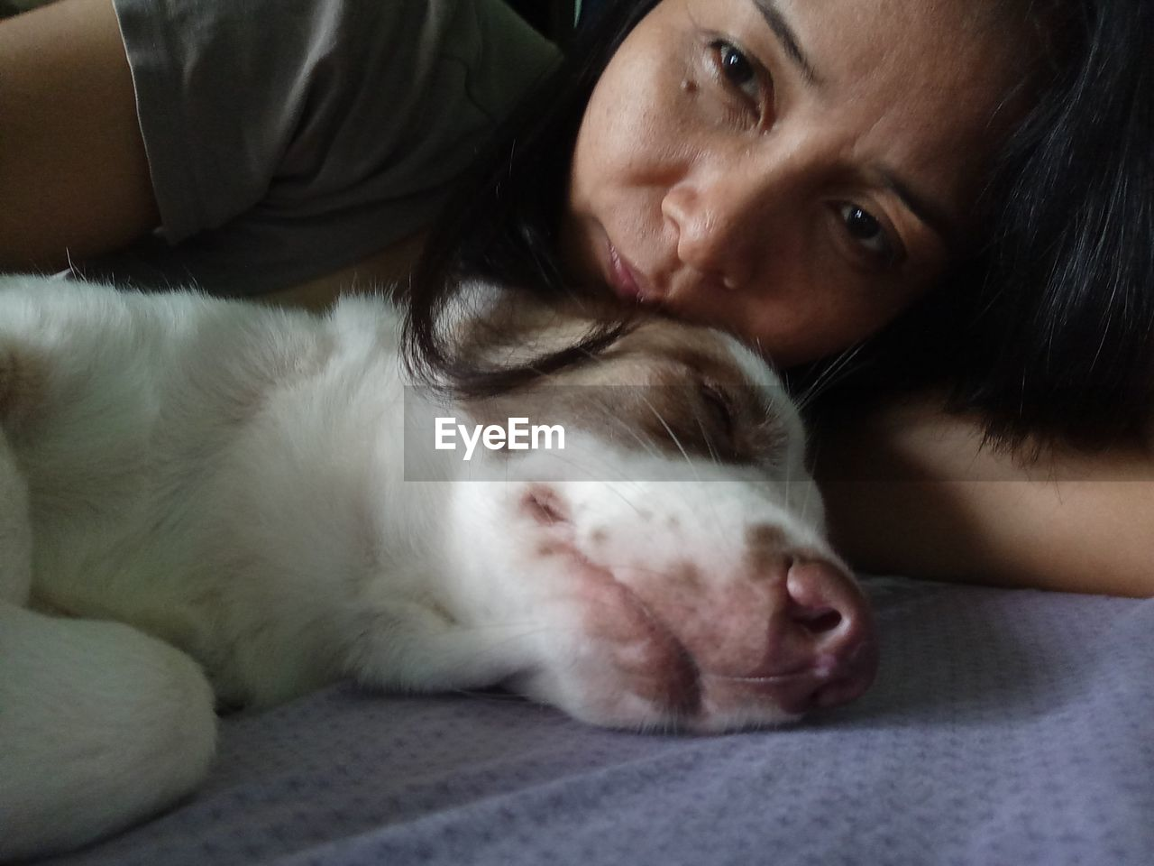 Close-Up Of Mature Woman With Dog Lying On Bed At Home