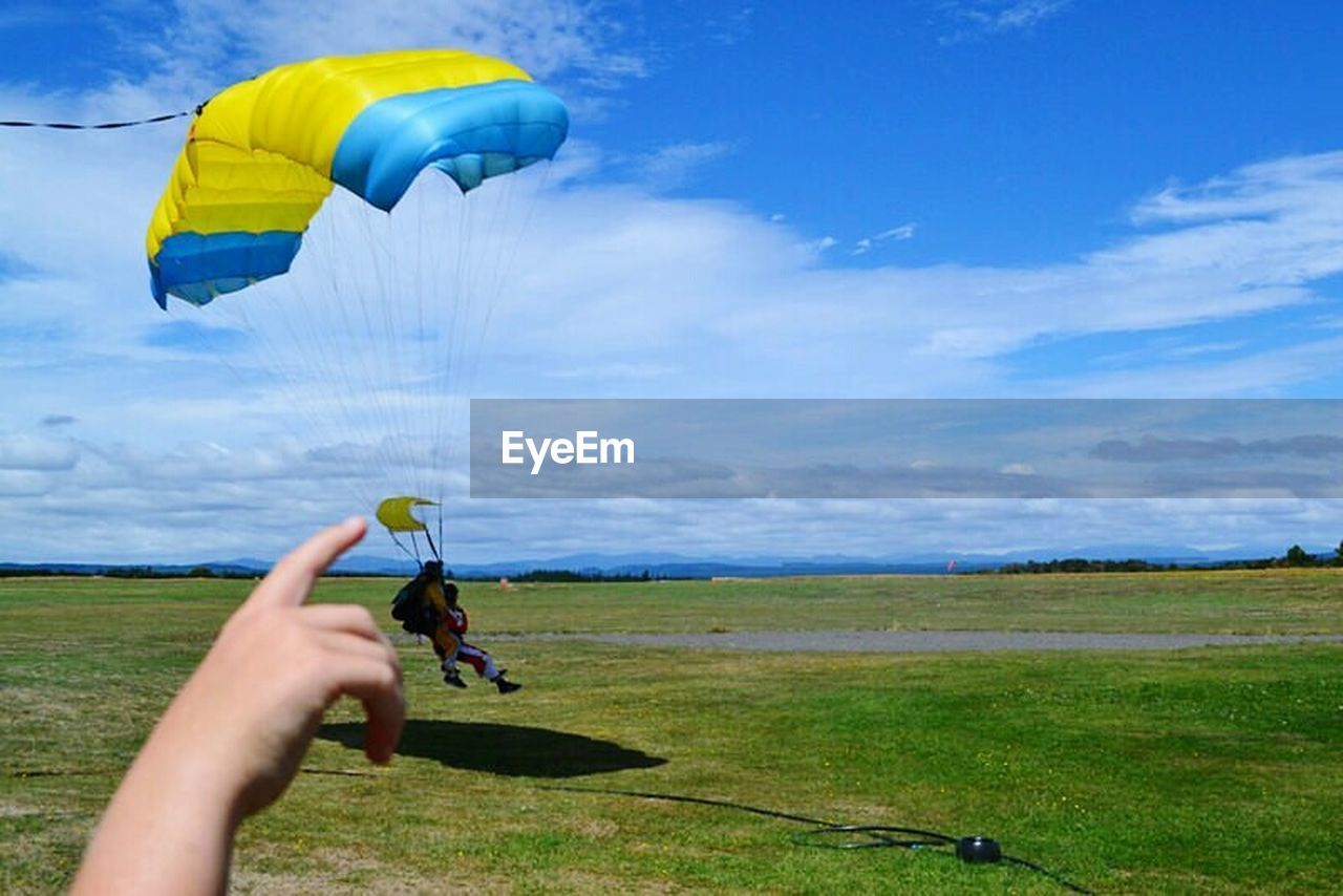 one person, leisure activity, real people, field, unrecognizable person, holding, sky, cloud - sky, human hand, grass, men, lifestyles, outdoors, day, sport, nature, human body part, parachute, flying, golf course, people, adult