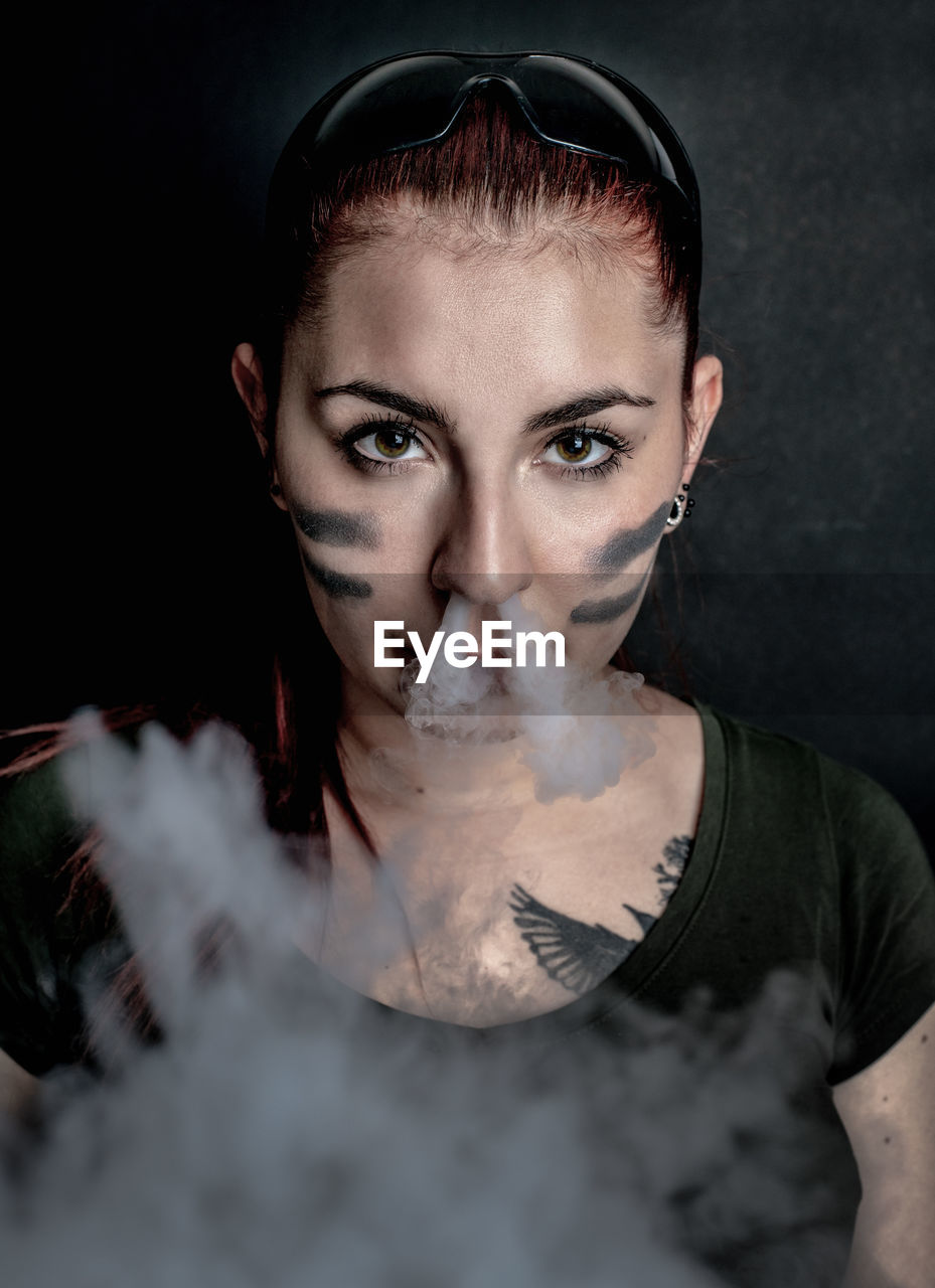 portrait, front view, one person, looking at camera, young adult, headshot, smoke - physical structure, indoors, real people, casual clothing, studio shot, holding, lifestyles, social issues, young women, black background, adult, beautiful woman