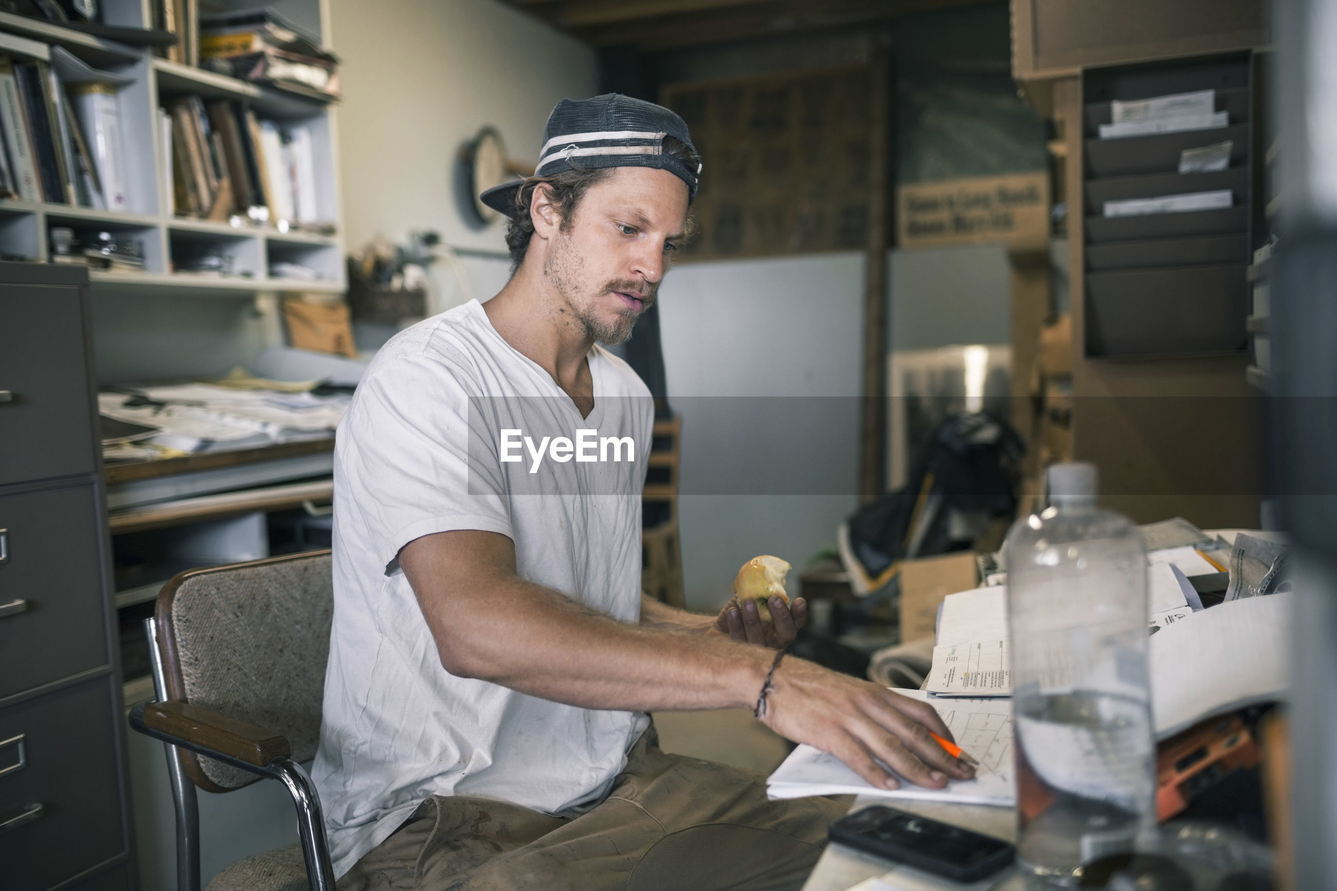 SIDE VIEW OF A MAN WORKING AT OFFICE