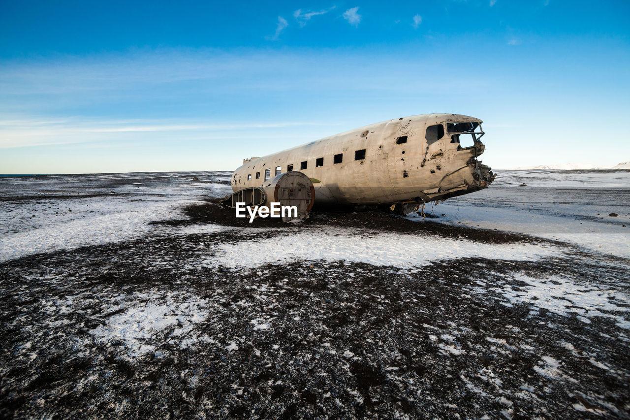 DAMAGED AIRPLANE ON BEACH DURING WINTER