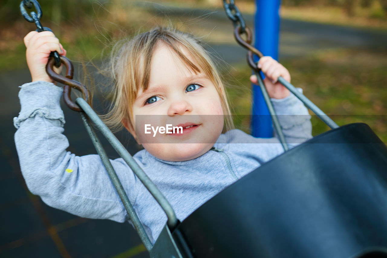 childhood, child, one person, portrait, innocence, real people, playground, females, front view, women, swing, holding, leisure activity, looking at camera, cute, smiling, casual clothing, headshot, girls, outdoor play equipment