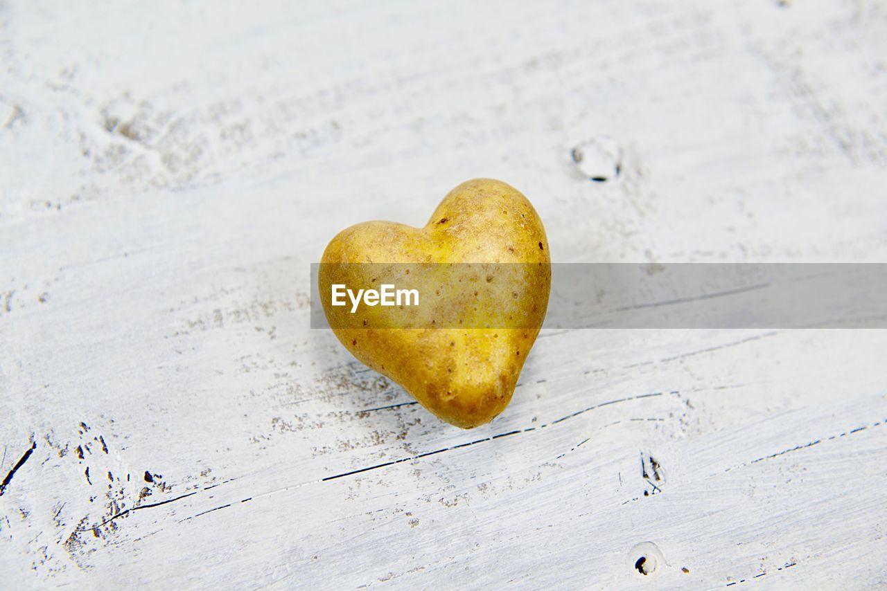High angle view of heart shape potato on table