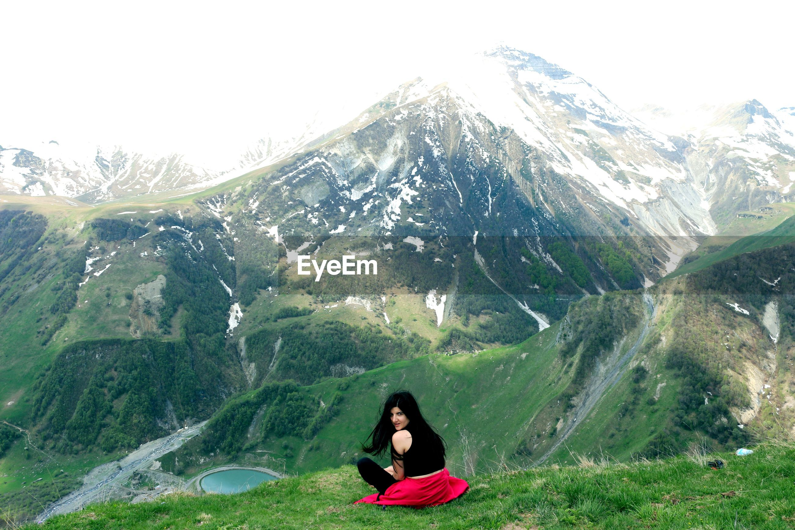 Portrait of woman sitting against mountain
