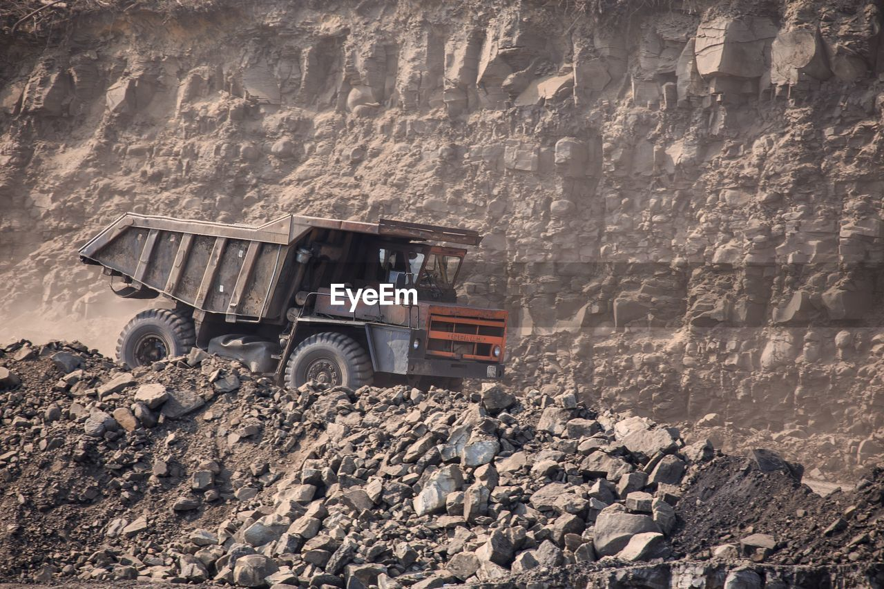 transportation, land vehicle, mode of transportation, rock, day, rock - object, solid, nature, construction industry, truck, no people, landscape, dirt, land, industry, outdoors, mountain, environment, machinery, bulldozer, mud, formation