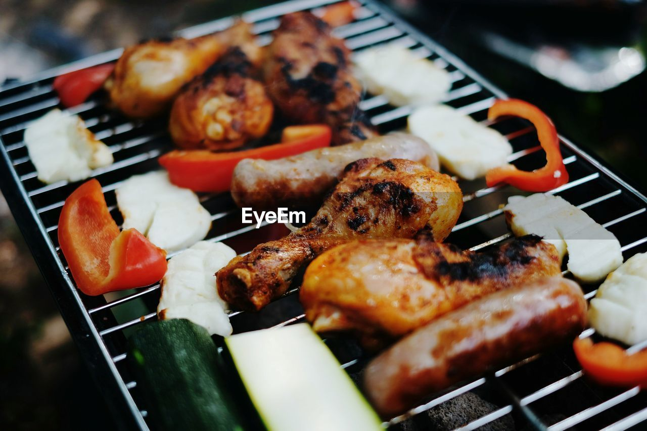 Close-up of chicken wings and vegetables on barbecue grill