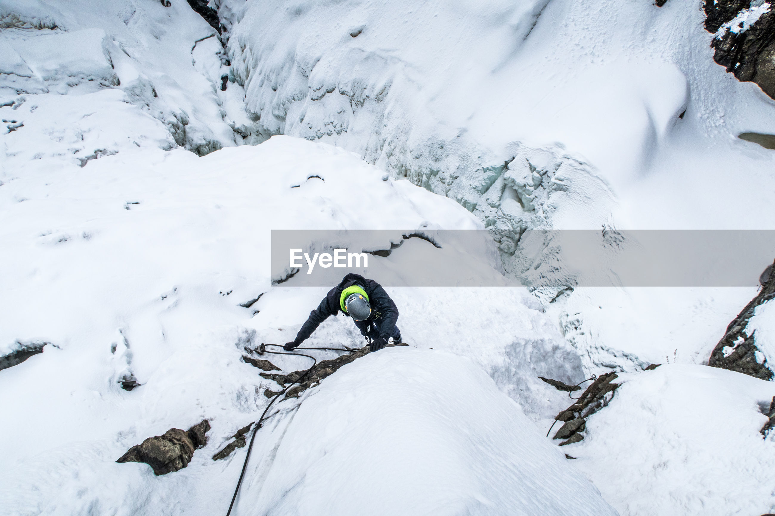High angle view of man climbing on snowcapped mountain
