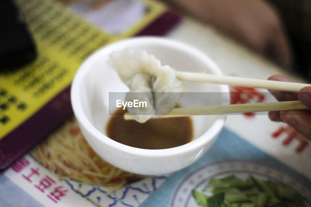 CLOSE-UP OF HAND HOLDING BOWL OF SOUP