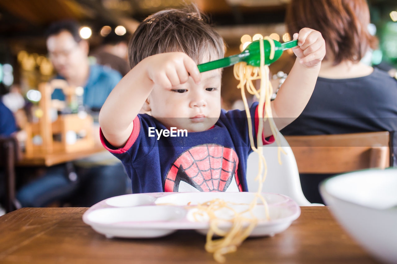 Cute Baby Boy Playing With Noodles At Table In Restaurant