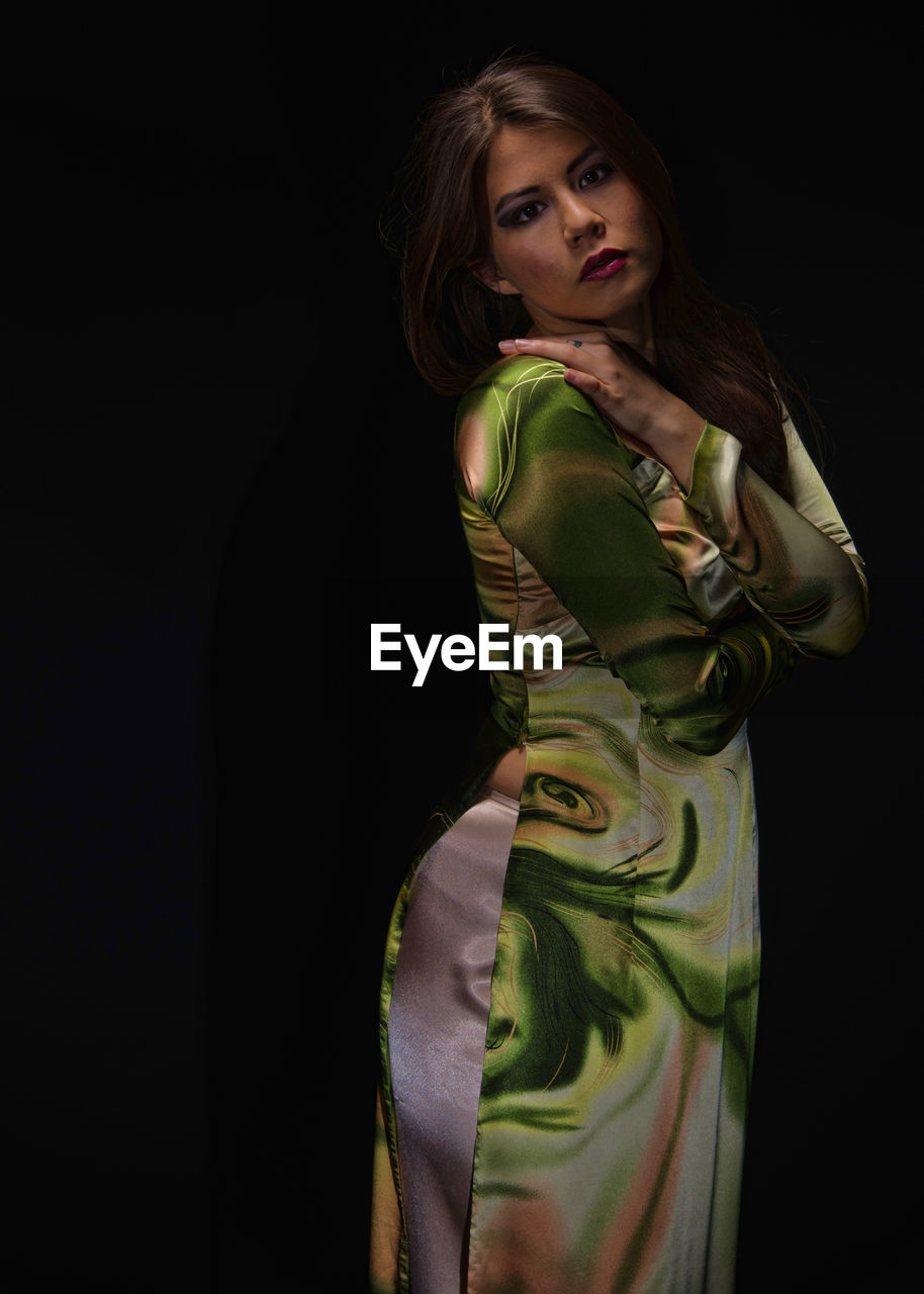 studio shot, black background, beautiful woman, fashion, young adult, fashion model, young women, portrait, looking at camera, one person, standing, beauty, beautiful people, glamour, night, lifestyles, women, one young woman only, indoors, adult, people, adults only