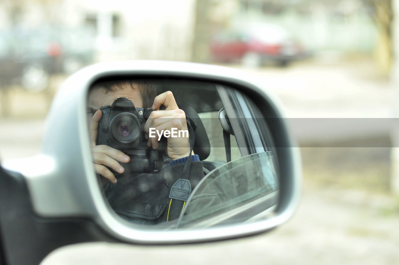 Reflection Of Man Photographing With Camera Seen In Side-View Mirror