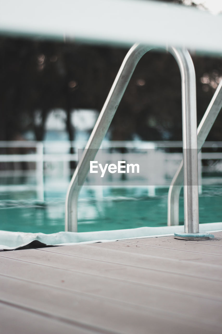Close-up of railing by swimming pool