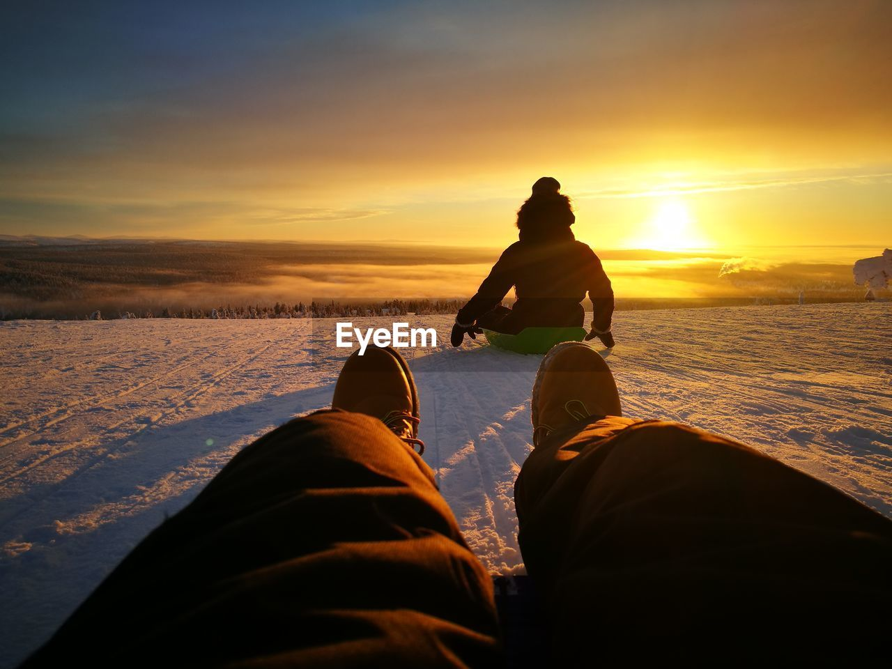 Friends tobogganing on snow covered hill against orange sky