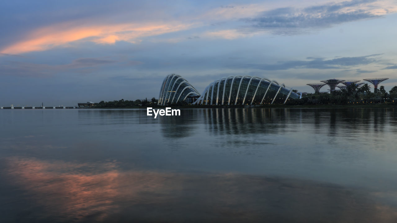 water, sky, cloud - sky, built structure, reflection, architecture, nature, waterfront, sunset, beauty in nature, no people, scenics - nature, lake, tranquility, travel destinations, building exterior, outdoors, connection, tranquil scene, arch bridge