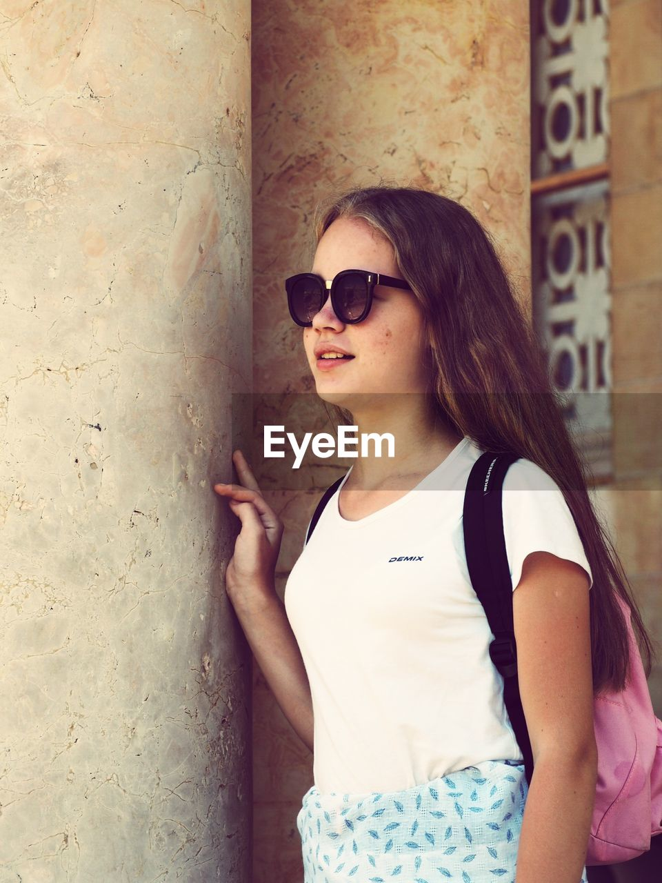 Girl With Backpack Wearing Sunglasses While Standing Against Wall