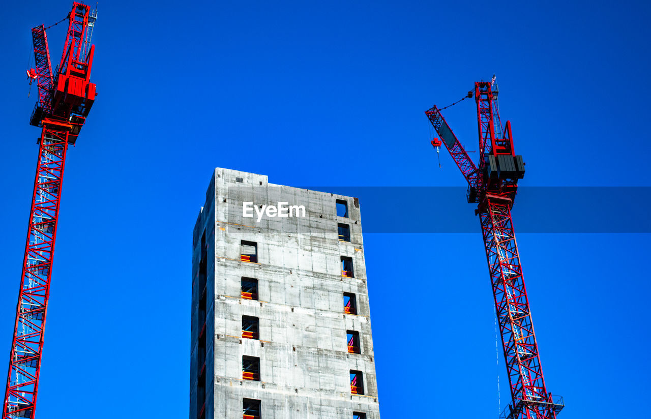 crane - construction machinery, architecture, construction industry, machinery, clear sky, blue, construction site, sky, built structure, development, low angle view, industry, building exterior, nature, tall - high, day, construction equipment, building, outdoors, no people