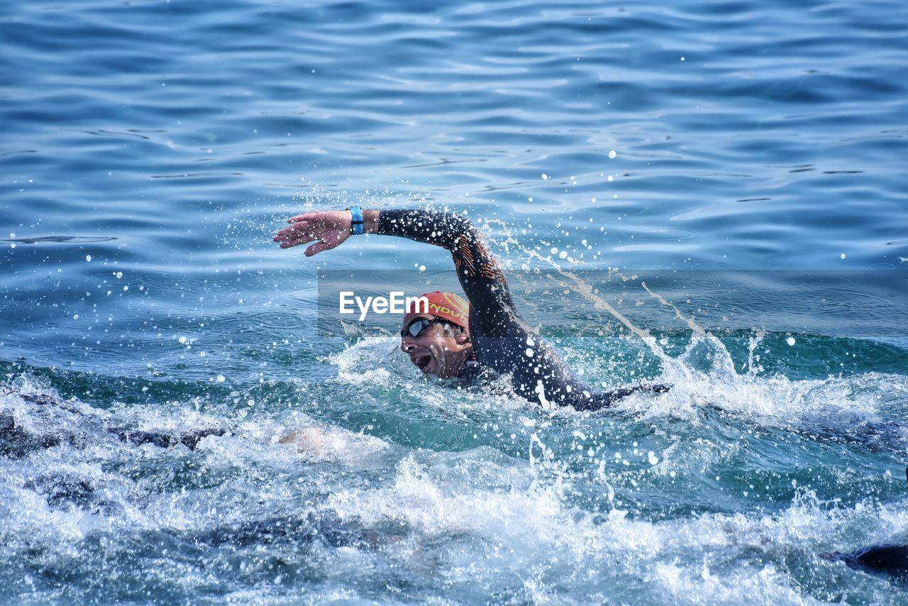 water, lifestyles, sea, real people, motion, waterfront, leisure activity, sport, one person, swimming, men, weekend activities, beauty in nature, day, nature, splashing, outdoors, healthy lifestyle, eyewear, physical activity, arms raised, human arm