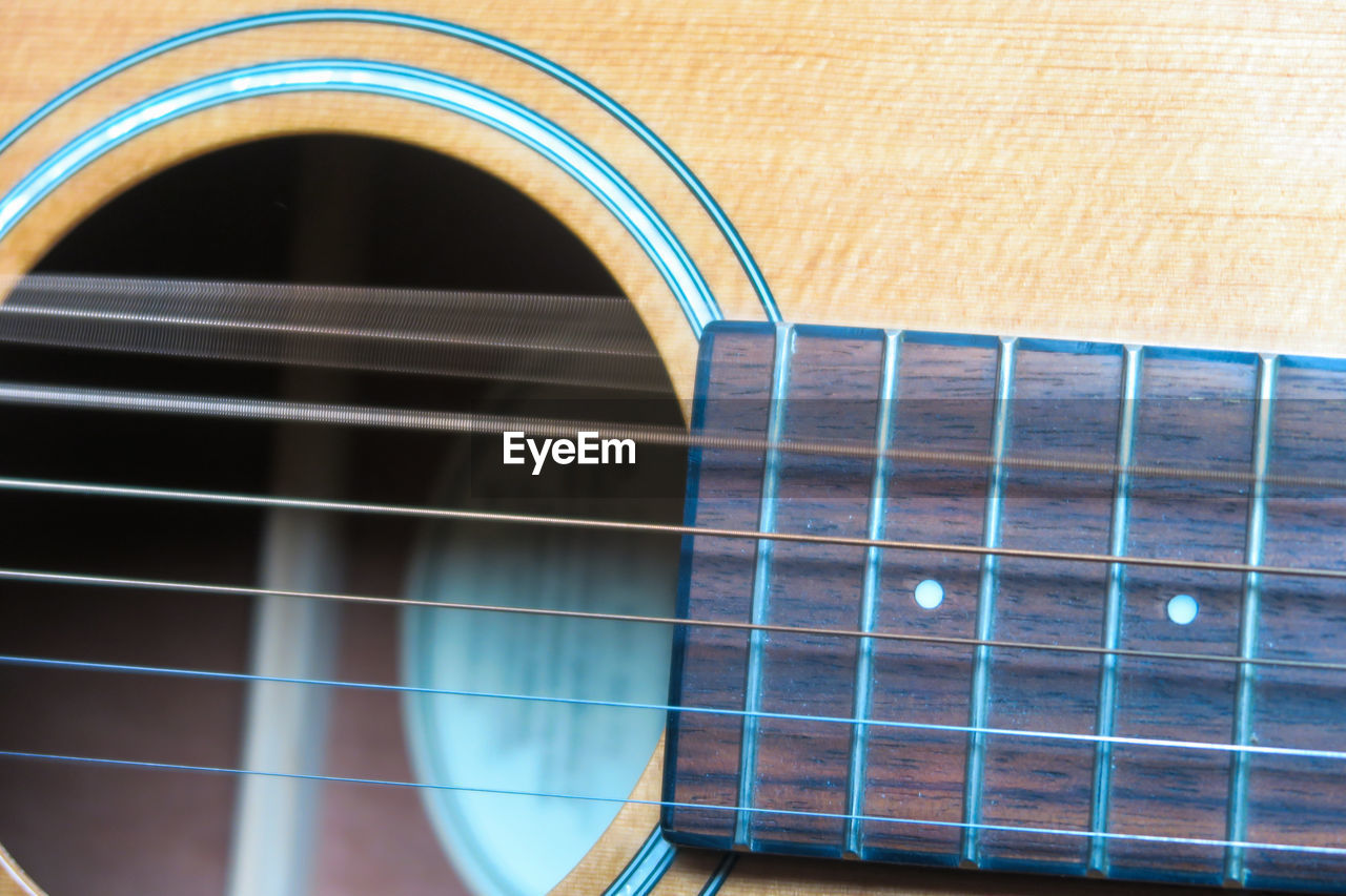 musical instrument, arts culture and entertainment, string instrument, indoors, music, musical equipment, musical instrument string, no people, guitar, close-up, pattern, acoustic guitar, arch, string, full frame, brown, high angle view, selective focus, fretboard, metal