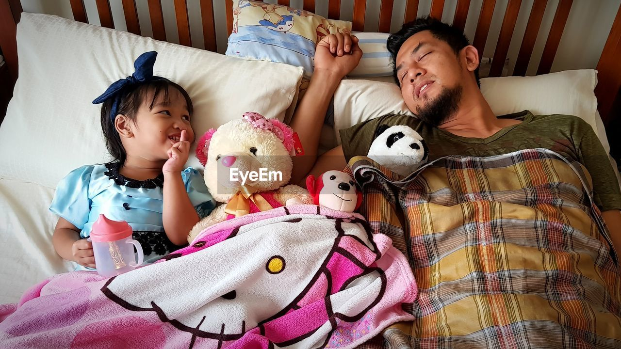 High Angle View Of Father And Daughter Sleeping On Bed At Home