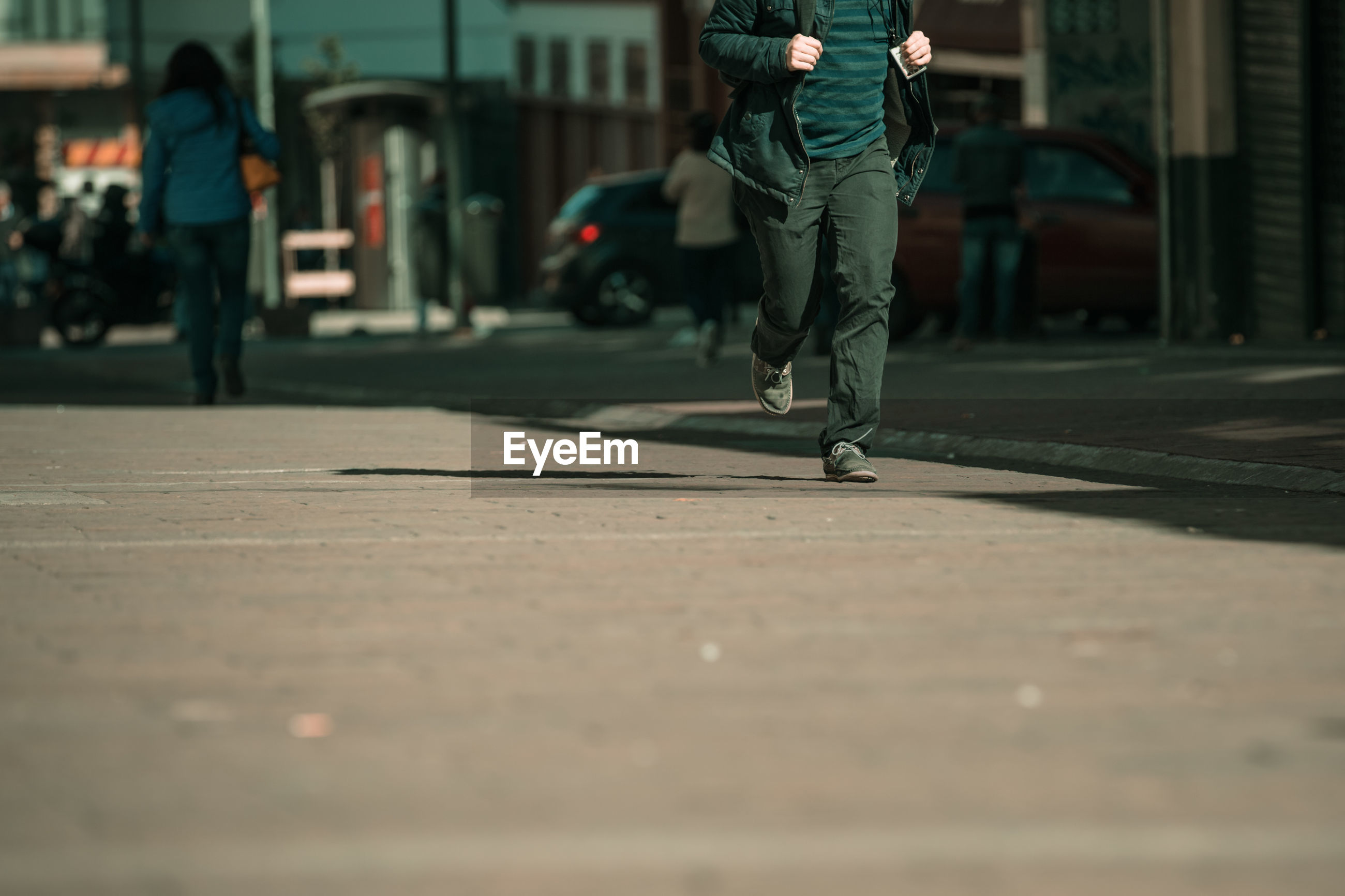Low section of man walking on street in city