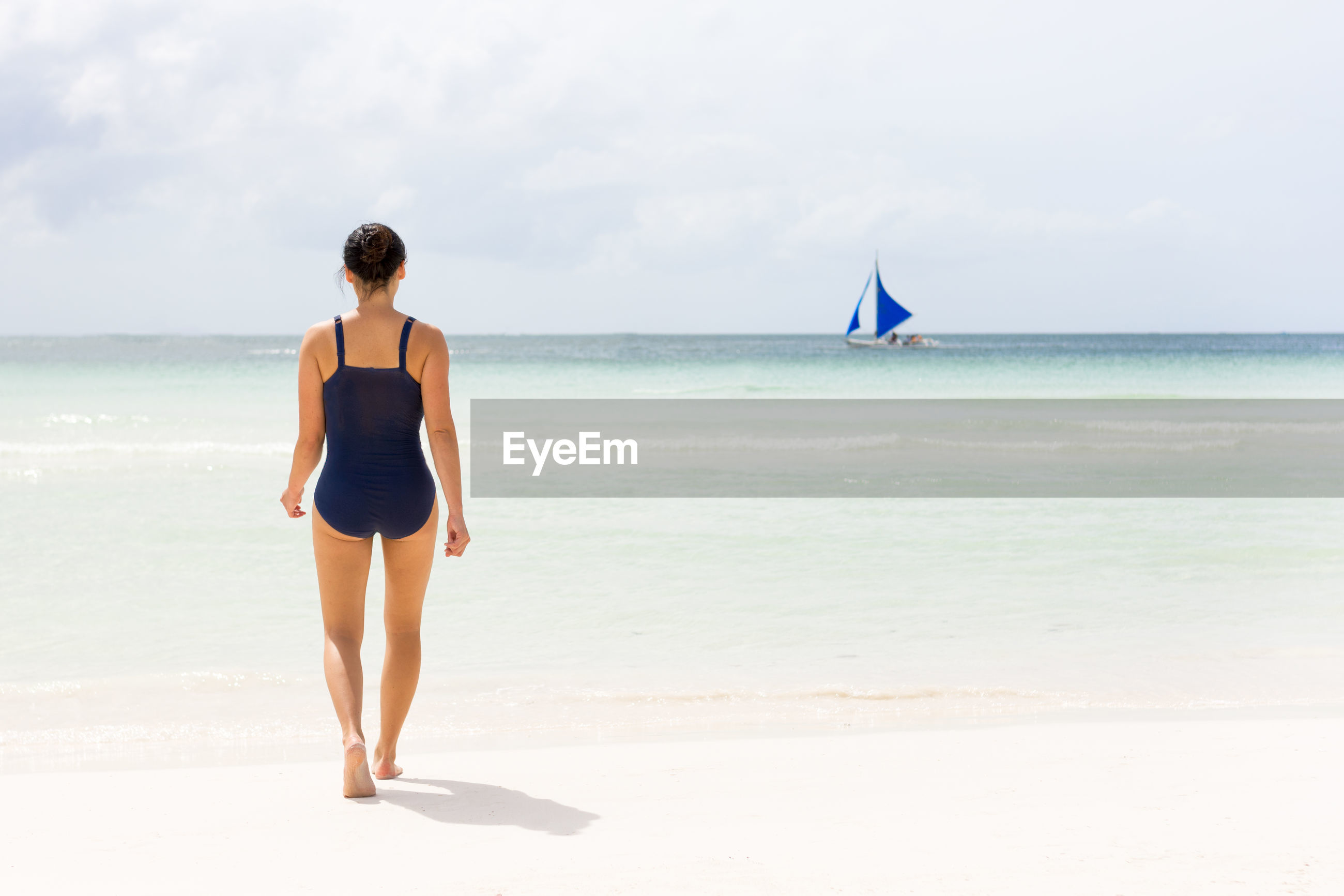 Rear view of woman in swimwear walking at beach