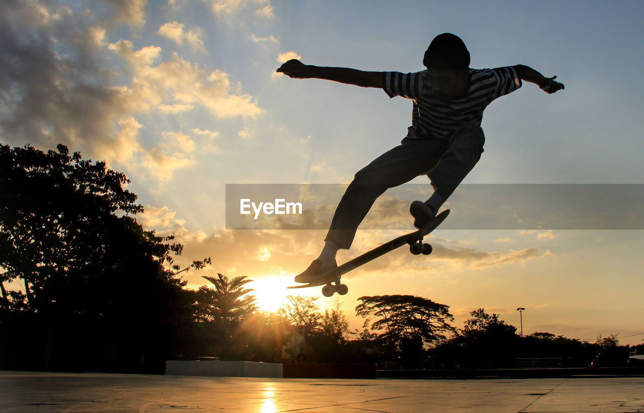 Silhouette man with skateboard jumping against sky during sunset