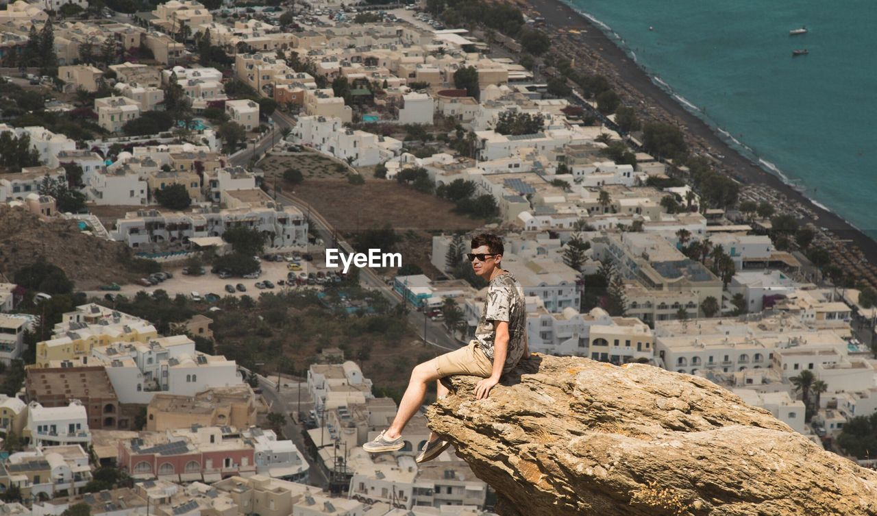 View Of Man Sitting On Rock Over View Of A City