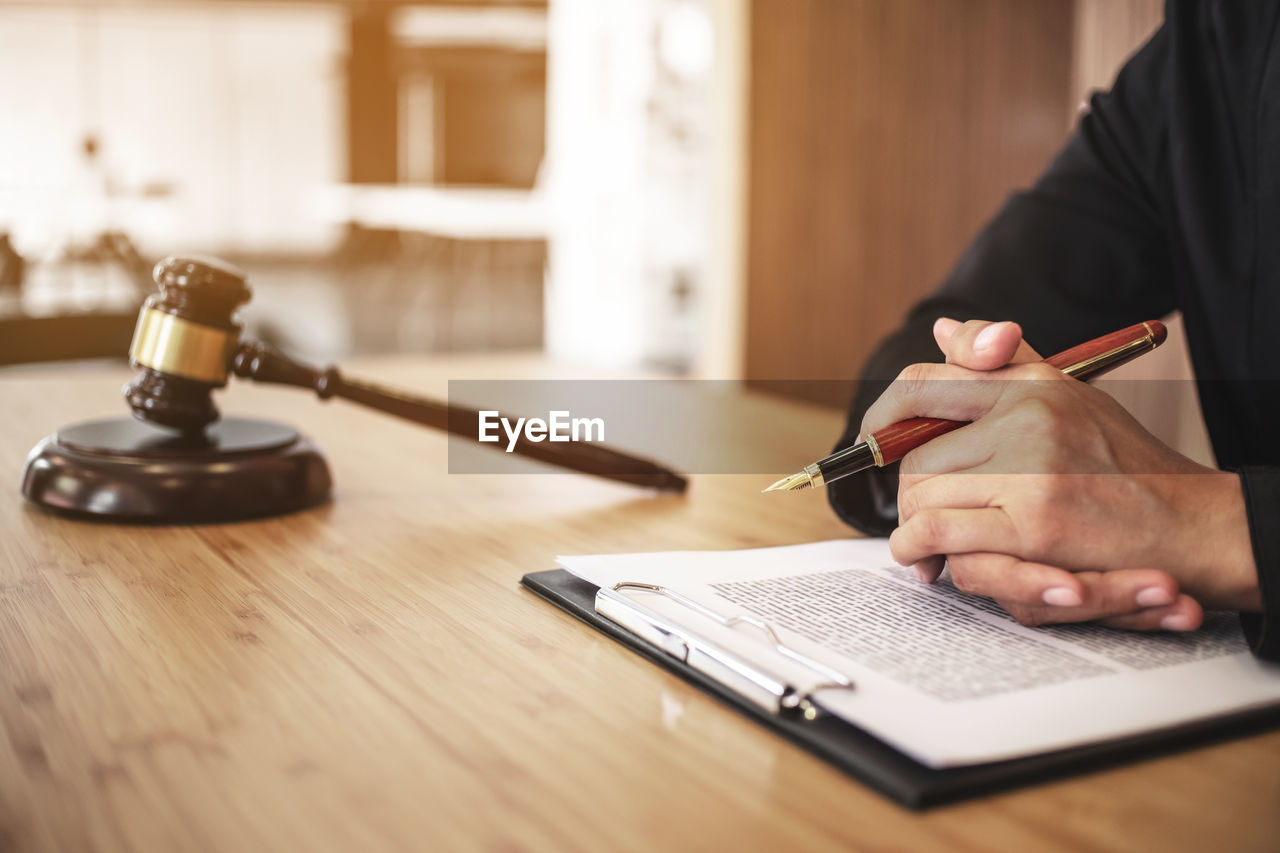 Midsection of lawyer reading document on desk in office