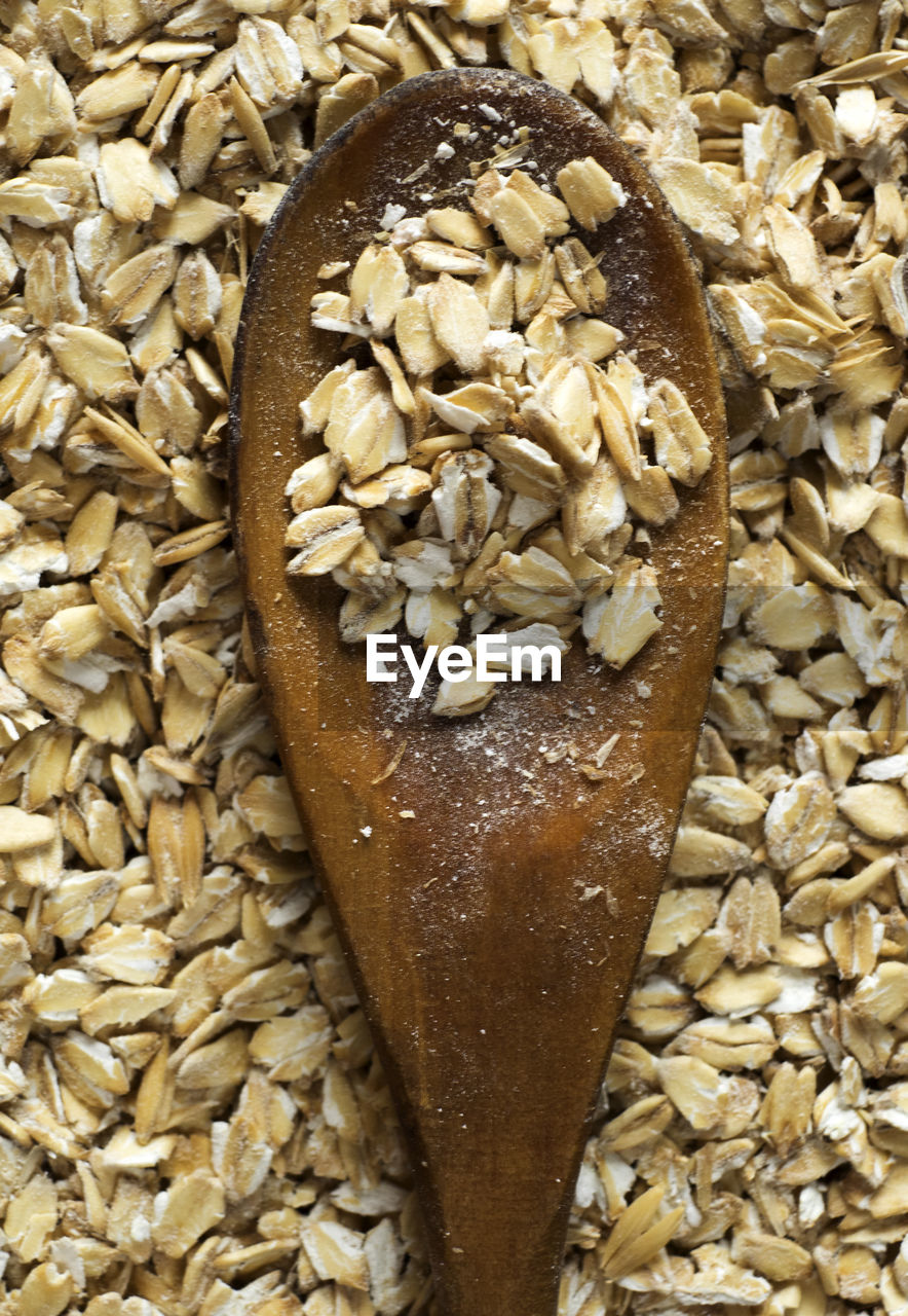 High angle view of wooden spoon on wheat grain