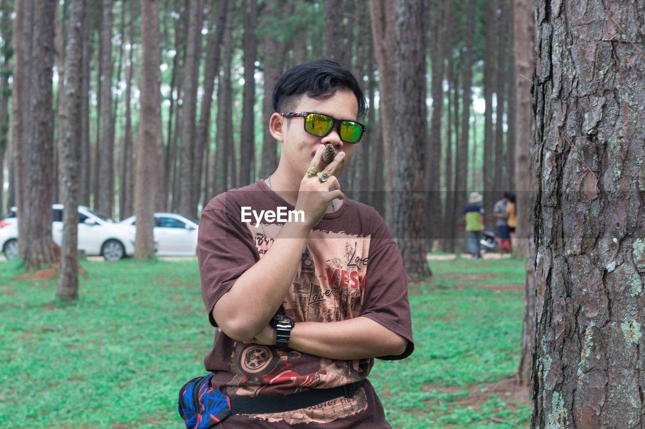 tree, tree trunk, one person, trunk, plant, casual clothing, holding, young men, young adult, land, front view, day, focus on foreground, forest, portrait, nature, leisure activity, glasses, standing, outdoors, woodland, teenager