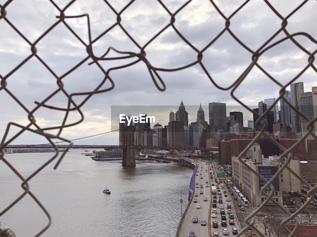 built structure, architecture, building exterior, city, water, fence, building, sky, cityscape, boundary, barrier, office building exterior, transportation, cloud - sky, skyscraper, chainlink fence, travel destinations, nature, no people, tall - high, modern, outdoors, bridge - man made structure, financial district