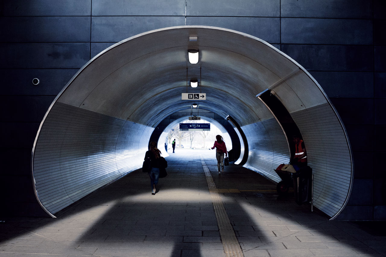 architecture, tunnel, real people, walking, direction, the way forward, arch, indoors, built structure, men, group of people, illuminated, transportation, footpath, lifestyles, rear view, people, motion, subway, full length, underground walkway, underpass, flooring, ceiling