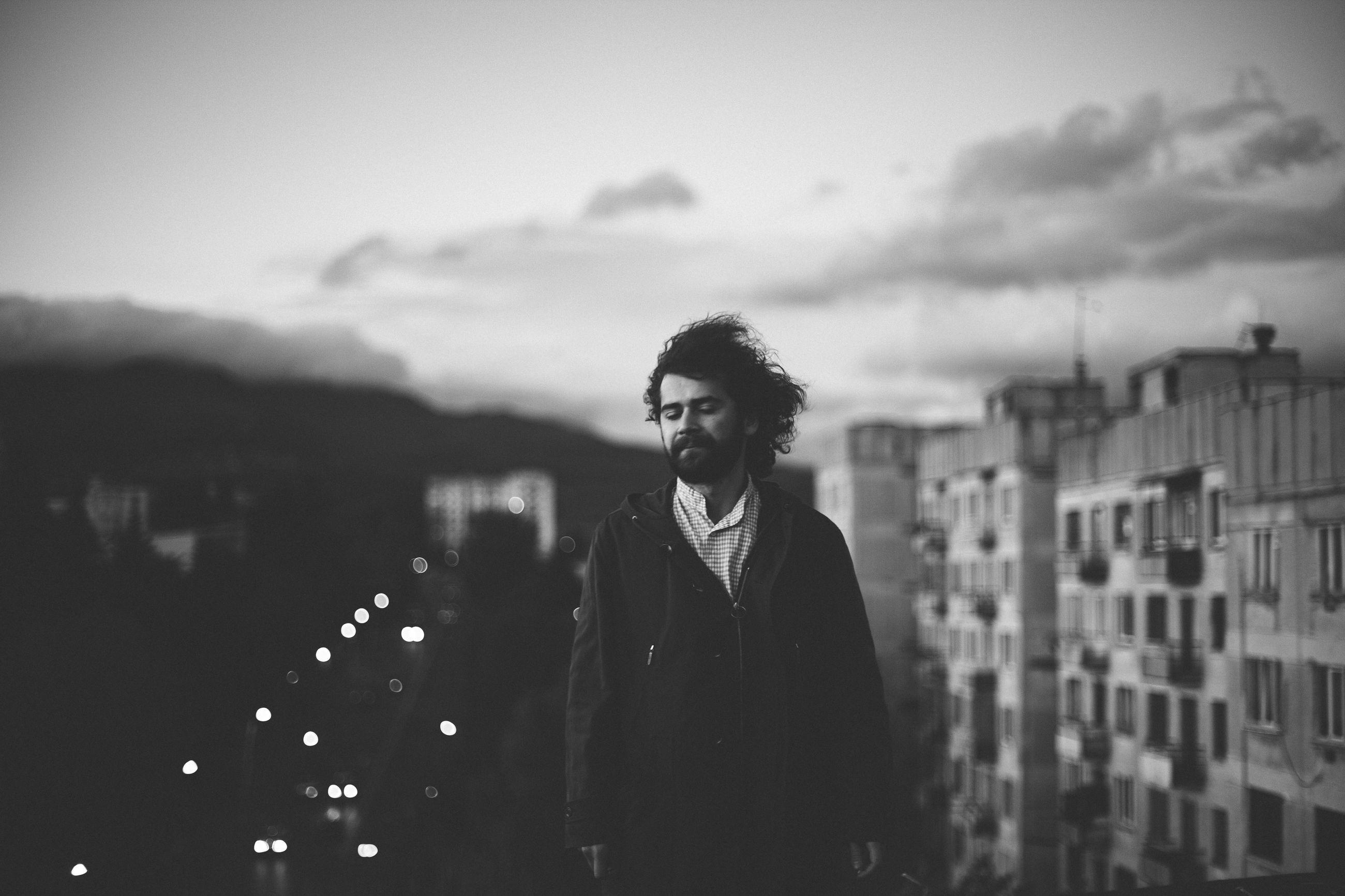 Man standing against buildings in city