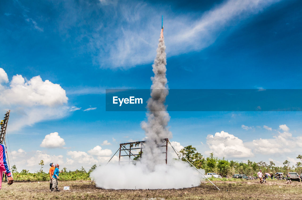 People Looking At Rocket While Standing On Field Against Blue Sky