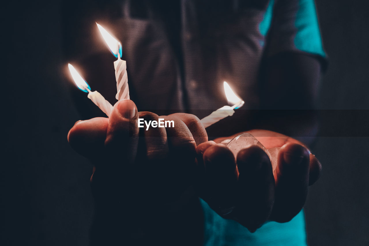 Midsection Of Man Holding Burning Candles