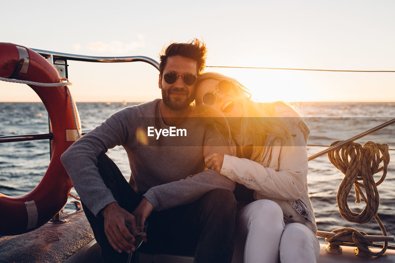 Portrait Of Smiling Couple Sitting In Boat On Sea Against Sky